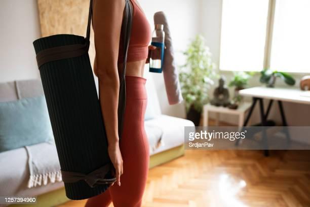 女性はヨガマットでリビングルームに来て、運動の準備をします - エクササイズマット ストックフォトと画像