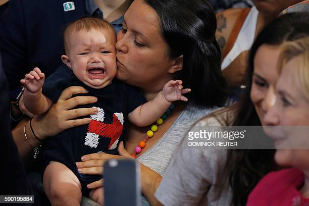A woman comforts a baby wearing a onesie with the campaign logo for Democratic presidential nominee Hillary Clinton at a voter registration rally...