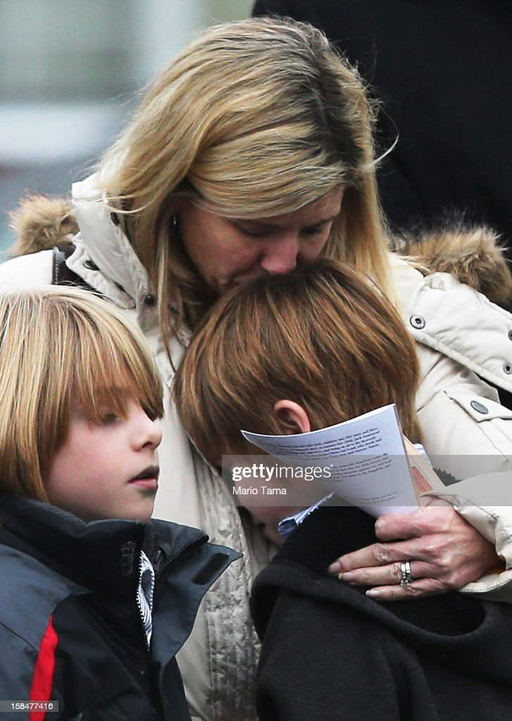 A woman comforts a boy as mourners depart Honan Funeral Home after the funeral for six-year-old Jack Pinto on December 17, 2012 in Newtown Connecticut. Pinto was one of the 20 students killed in the Sandy Hook Elementary School mass shooting.