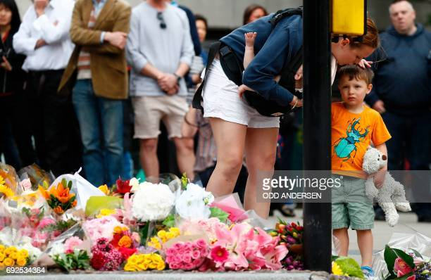 A woman comforts a child after laying flowers at a pedestrian crossing on the south side of London Bridge close to Borough Market in London on June 5...