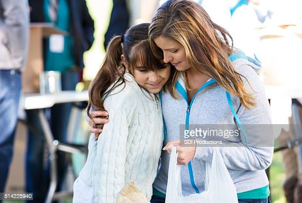 woman comforts daughter at clothing drive - armoede stockfoto's en -beelden