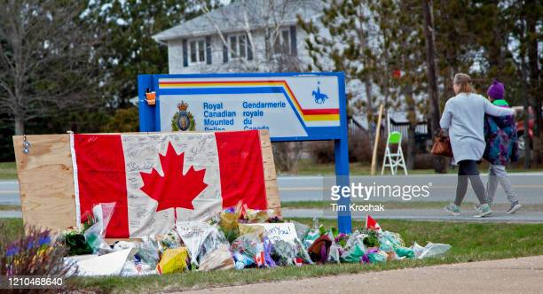 Woman comforts her daughter after they placed flowers at an impromptu memorial in front of the RCMP detachment April 20, 2020 in Enfield, Nova...
