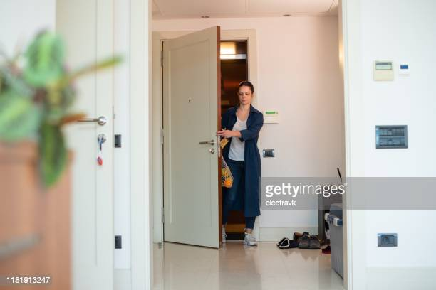 woman coming home after grocery shopping - chegada imagens e fotografias de stock