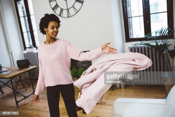 woman coming home, throwing coat on sofa, smiling - llegada fotografías e imágenes de stock
