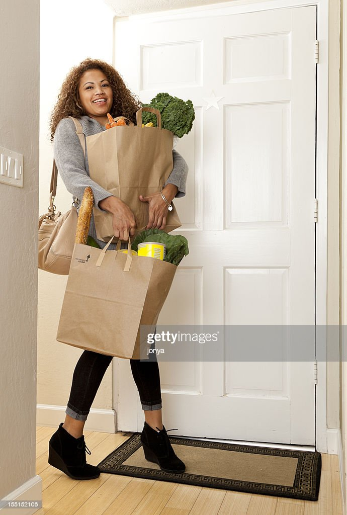 woman coming home with grocery bags : Stock Photo