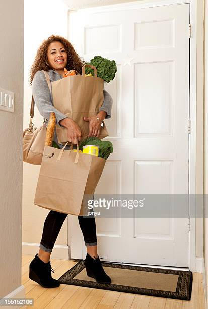woman coming home with grocery bags