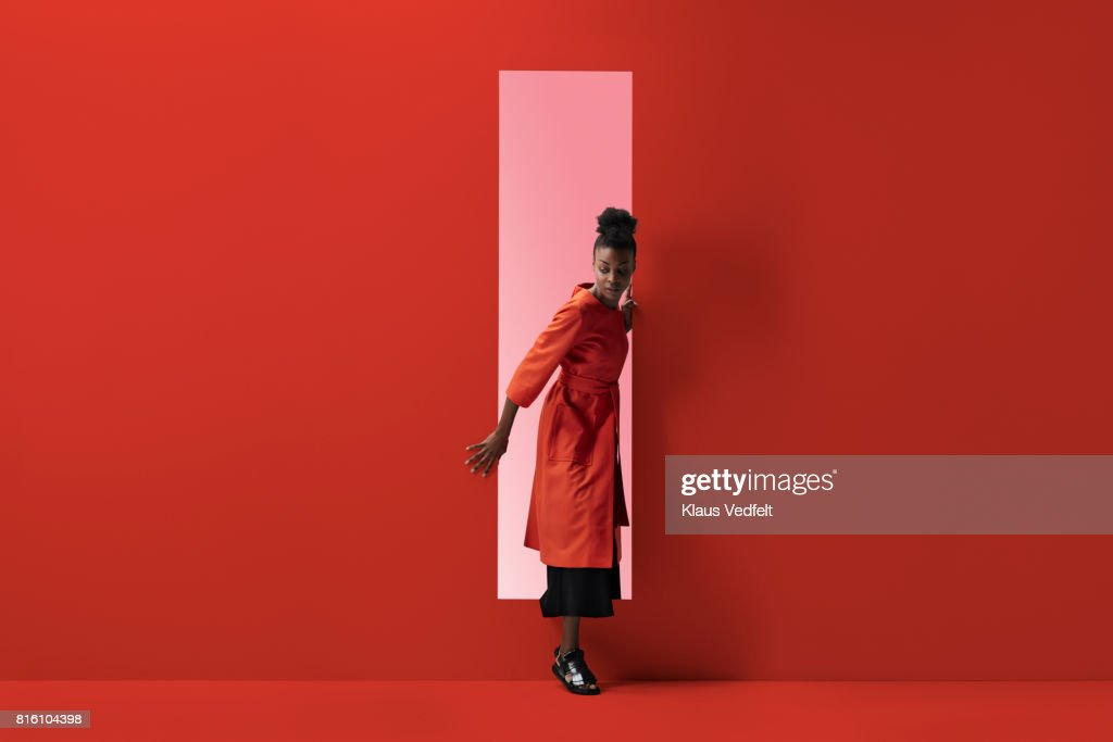 Woman coming out of rectangular opening in coloured wall : ストックフォト