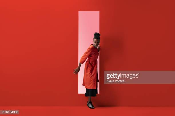 woman coming out of rectangular opening in coloured wall - rot stock-fotos und bilder