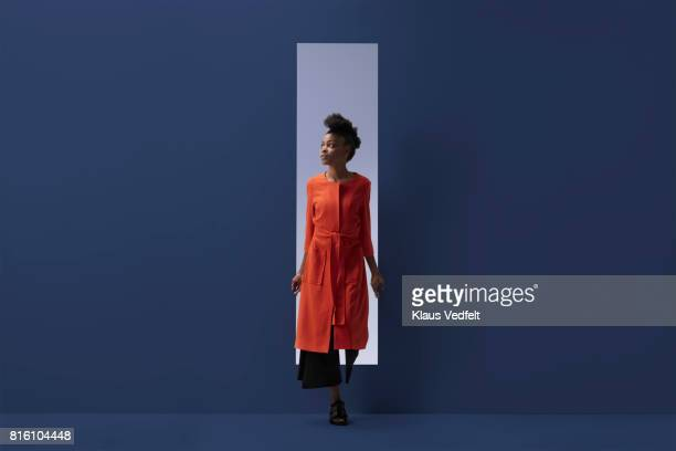 woman coming out of rectangular opening in coloured wall - orange farbe stock-fotos und bilder