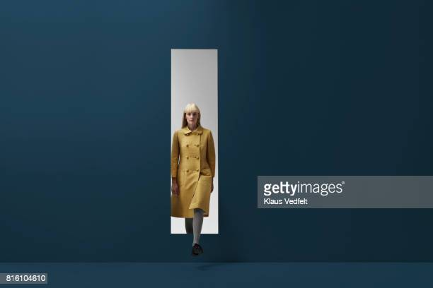 woman coming out of rectangular opening in coloured wall - caucasian appearance stock pictures, royalty-free photos & images