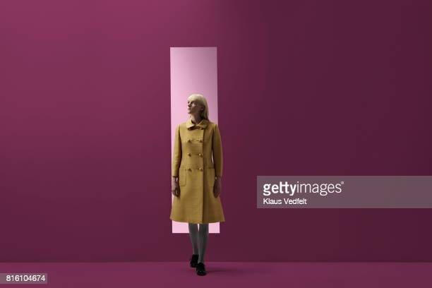 woman coming out of rectangular opening in coloured wall - só uma mulher jovem imagens e fotografias de stock