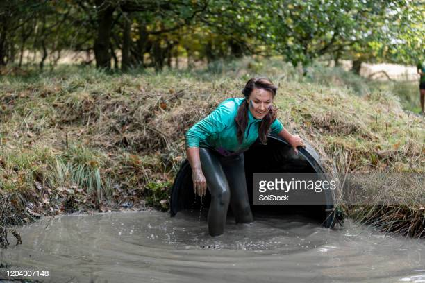 woman coming out of water tunnel on outside obstacle course - caucasian appearance stock pictures, royalty-free photos & images
