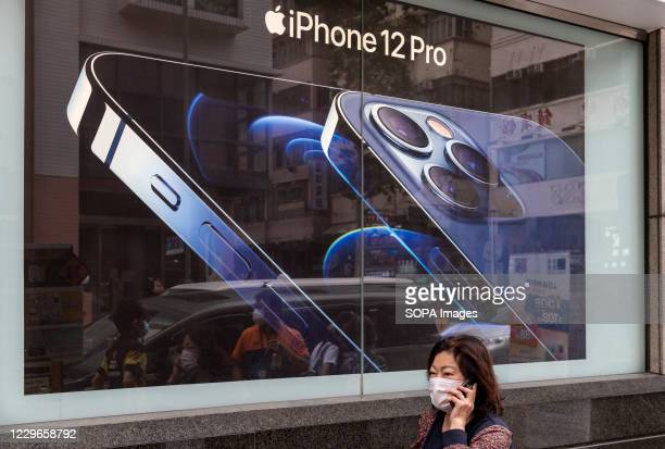 Woman communicating on a phone walking past an American multinational technology company Apple Iphone 12 Pro advertisement in Hong Kong.