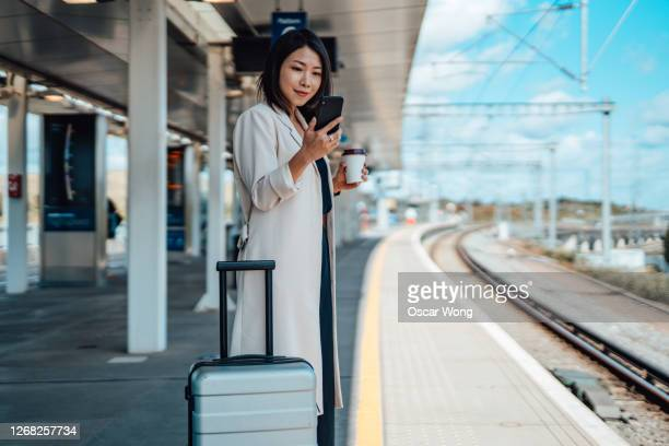 woman commuter using public transport with face mask - railroad station platform stock pictures, royalty-free photos & images