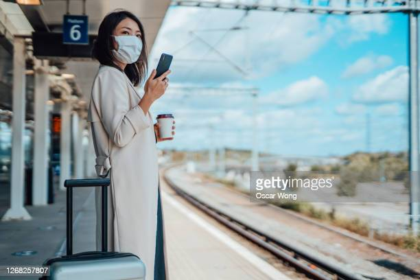 woman commuter using public transport with face mask - railway station stock pictures, royalty-free photos & images