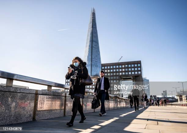 woman commutes to work on london bridge with protective face mask - uk stock pictures, royalty-free photos & images