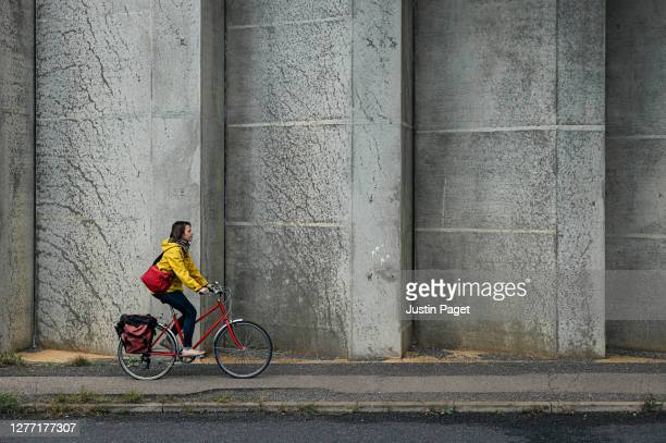 woman commuting to work on her bicycle - commuter stock pictures, royalty-free photos & images