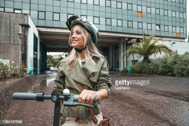 woman commuting to work with electric scooter wearing an helmet - electric scooter stock pictures, royalty-free photos & images