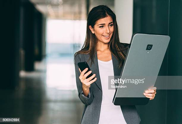 Woman comparing a normal smart phone to a huge one