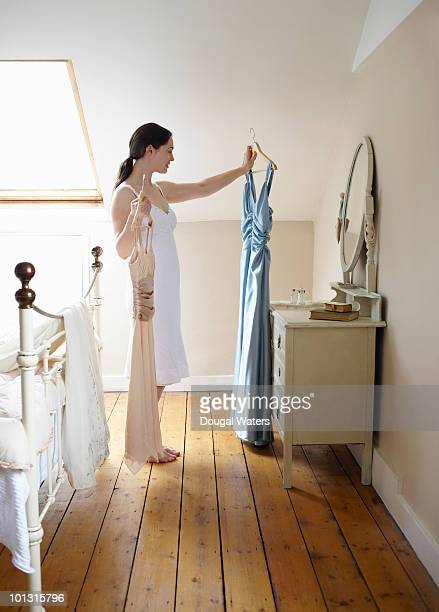 woman comparing dresses. - women in slips stock photos and pictures