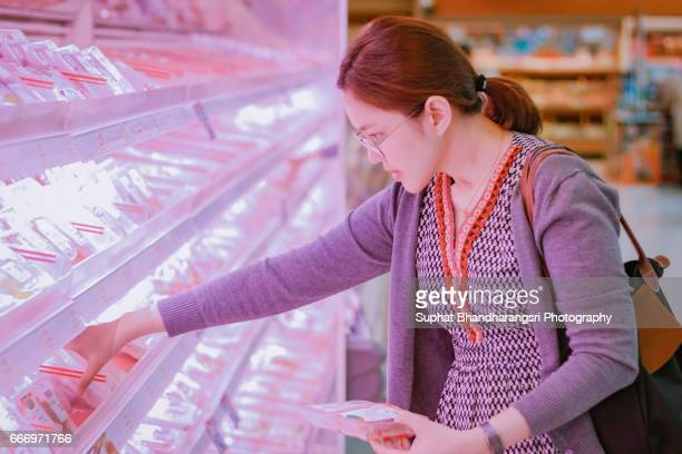 Woman comparing fresh meats at supermarket