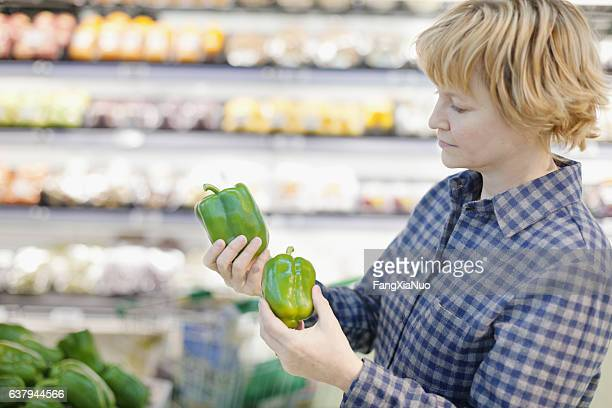 Woman comparing green bell peppers in grocery store produce aisle