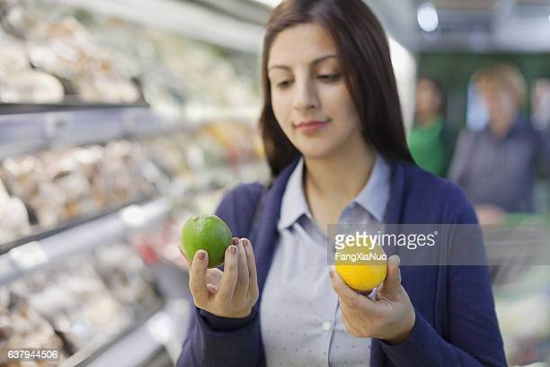 Woman comparing lemon and lime in grocery store produce aisle