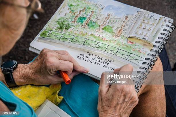 CATALUNYA BARCELONA BARCELONA CATALONIA SPAIN A woman completes her drawing with the inscription quoting 'I am not afraid drawing on the street'...
