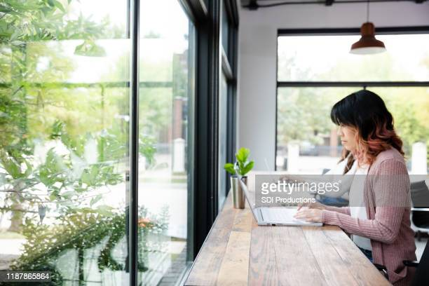 woman concentrates while using laptop - lush stock pictures, royalty-free photos & images