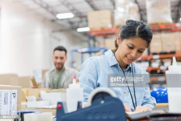 woman concentrates while working in distribution warehouse - post office stock pictures, royalty-free photos & images