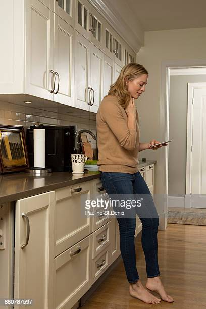 Woman concentrating whilst reading smartphone text in kitchen