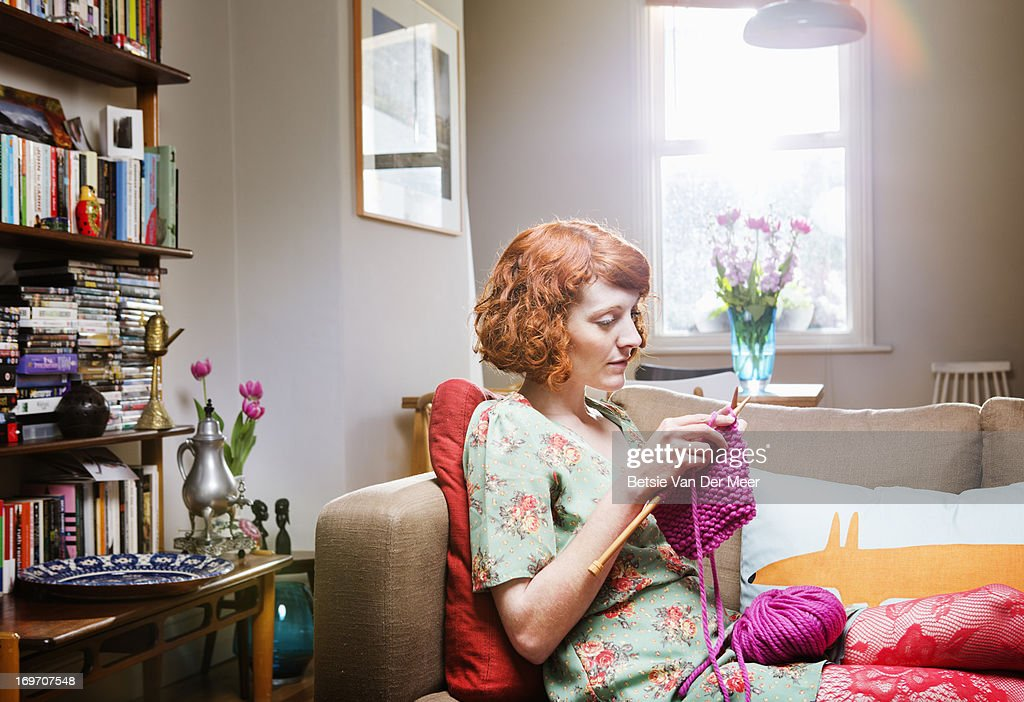Woman concentrating,knitting in livingroom. : Stock Photo