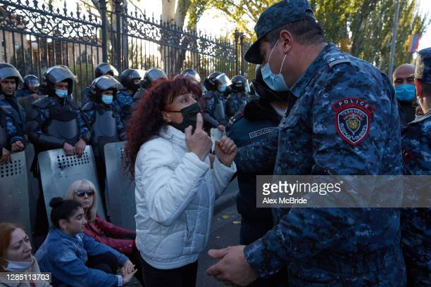 Woman confronts a police officer as protesters demand the removal of Armenian Prime Minister Nikol Pashinyan from office outside the Armenian...
