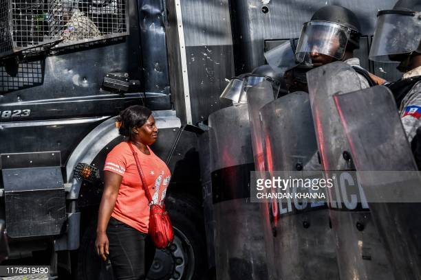 Woman confronts Haitian police during a protest march on the street to demand the resignation of the Haitian president in Port-au-Prince, Haiti on...
