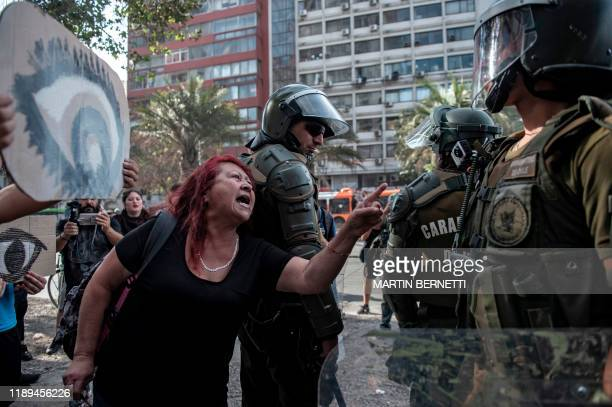 TOPSHOT A woman confronts riot police during a protest against Chilean President Sebastian Pinera's government with signs depicting eyes referring to...