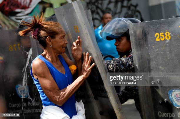 TOPSHOT A woman confronts riot police during a protest against the shortage of food amid Fuerzas Armadas avenue in Caracas on December 28 2017 As...