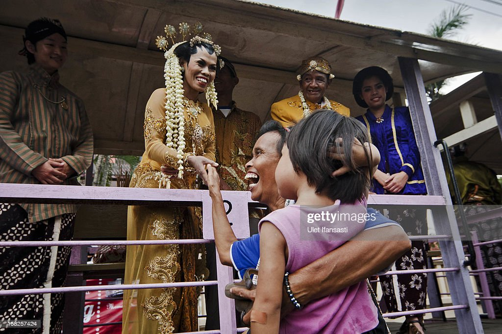 A woman congratulates a bride and groom during a mass wedding ceremony on December 12, 2012 in Yogyakarta, Indonesia. Twelve couples participated in a mass wedding as today saw a surge in marriage across the globe to mark the once in a century date of 12/12/12.
