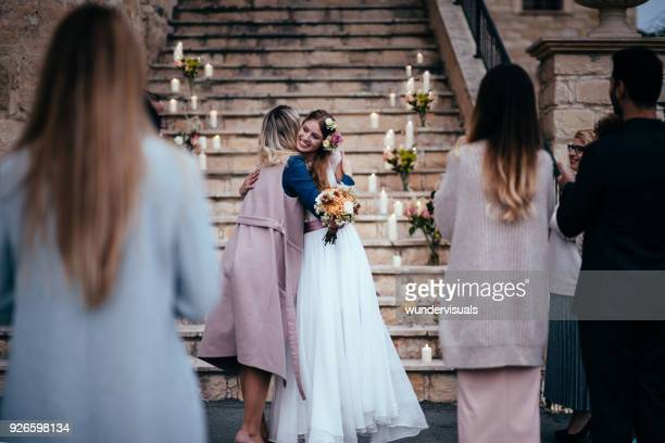 Woman congratulating bride at rustic cottage wedding reception