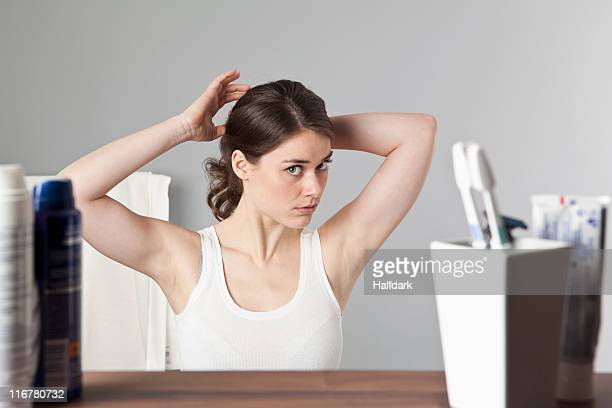 a woman considering her hairstyle - ajustar imagens e fotografias de stock