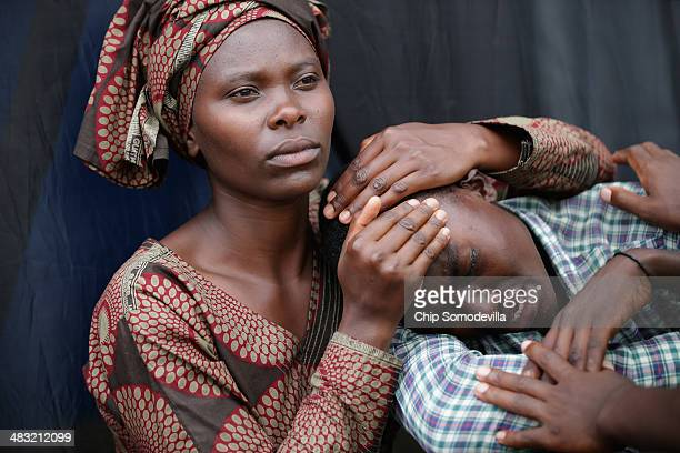 A woman consoles Bizimana Emmanuel during the 20th anniversary commemoration of the 1994 genocide at Amahoro Stadium April 7 2014 in Kigali Rwanda...
