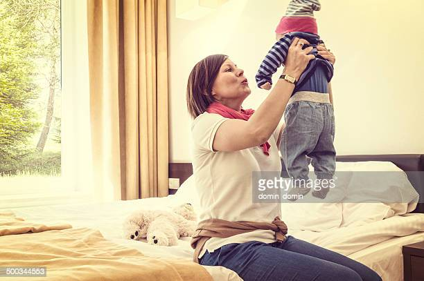 Woman consoling little child and raising baby up, vintage look
