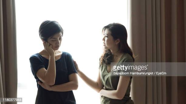 woman consoling sad female friend standing against window at home - compassionate eye stock pictures, royalty-free photos & images