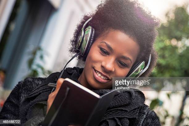 Woman consulting agenda and listening to music