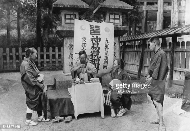 A woman consults a fortuneteller at the Inari or Fox Temple in Kyoto Japan Her elderly mother and son stand by to see if the omen is good The...