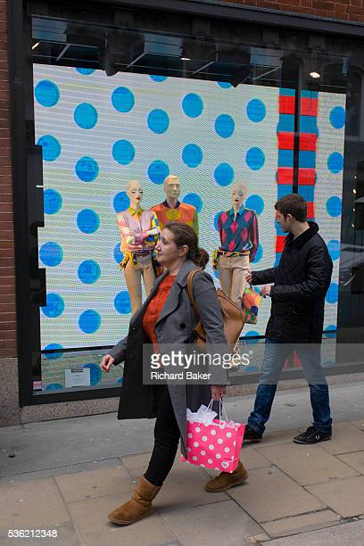 Woman consumer carrying a spotty shopping bag passes a window theme of dots in the window of Etro on Old Bond Street, central London. Walking past...