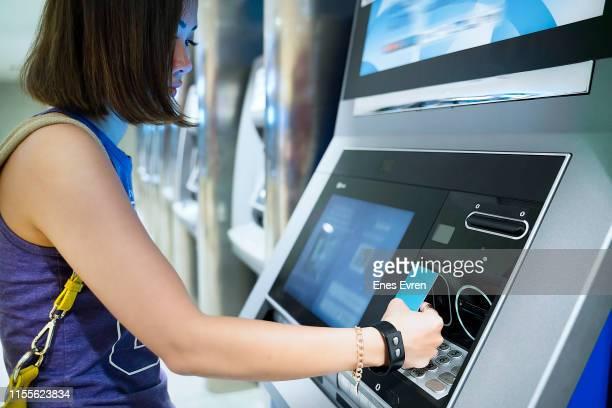 女性の非接触キャッシュマシンからお金を引き出す - セルフサービス ストックフォトと画像