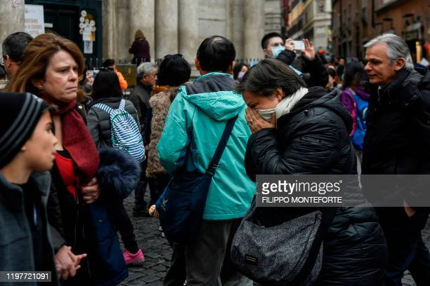 A woman contains her sneezing in her scarf by the Trevi fountain in downtown Rome on January 31 2020 The Italian government declared a state of...