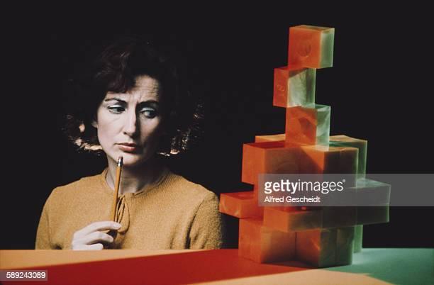 A woman contemplates a stack of building blocks circa 1980