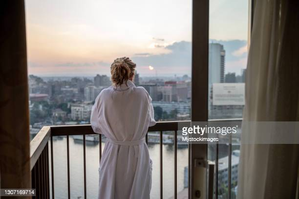 woman contemplates cairo city and the nile river at sunset - hotel stock pictures, royalty-free photos & images