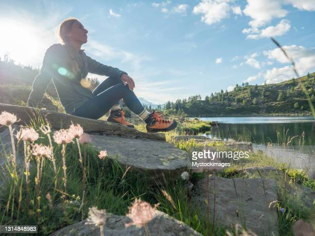 woman contemplates lake at sunrise - swiss alps stock pictures, royalty-free photos & images